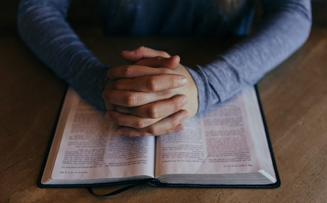 Hands clasped in prayer on open Bible