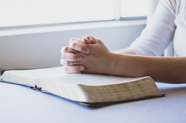 A person praying with their Bible