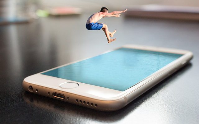 Photo montage of man jumping into a giant cell phone pool