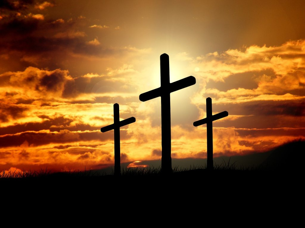 Three empty crosses in the setting sun